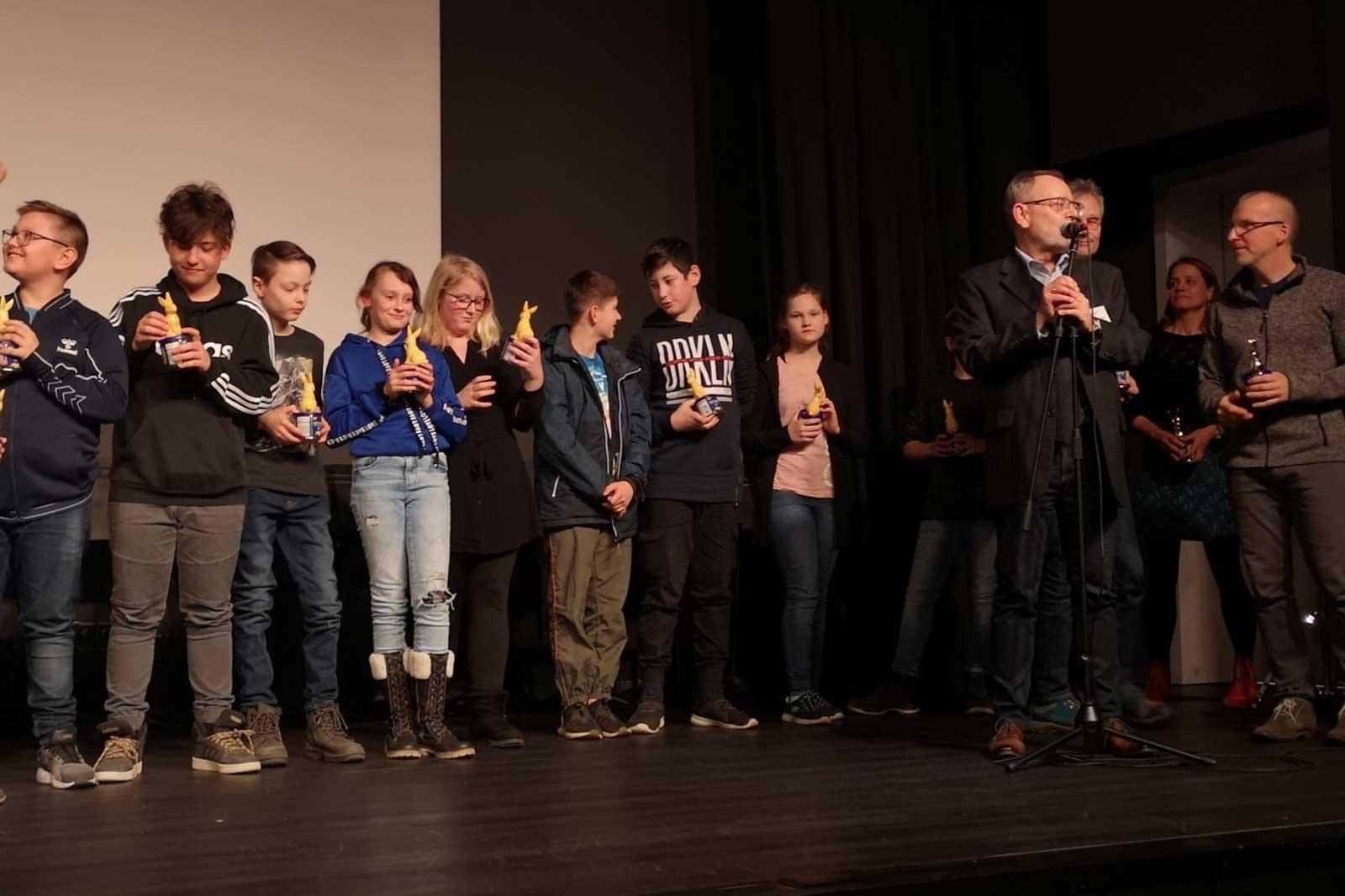 Kinder halten auf der Bühne den Preis